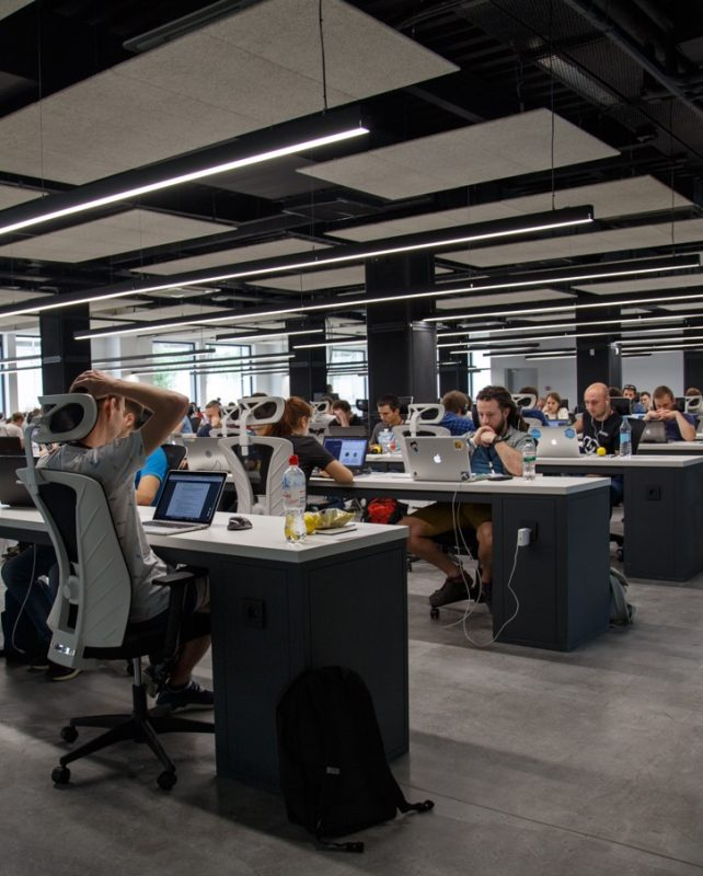 Öppet kontorslandskap där människor arbetar framför sina laptops